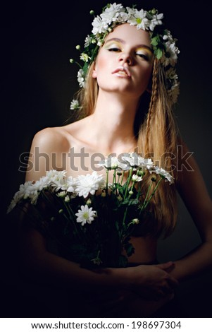 Waist up of sexy young woman with bouquet of daisies in her hands and flowers on her head, looking down - stock photo