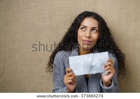 Waist Up of Smiling Young Woman with Curly Dark Hair Looking Excited and Holding White Envelope Wrapped with white Ribbon and Bow in Studio with Textured Beige Background and Copy Space - stock photo