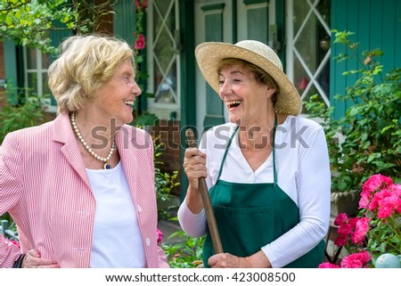 Waist Up of Two Senior Women Having Enjoyable Conversation and Laughing in Home Garden on Summer Day - stock photo