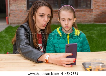 Waist Up of Woman and Girl Taking Selfie Portrait and Making Funny Facial Expressions with Modern Cell Phone While Sitting at Picnic Table Outdoors - stock photo