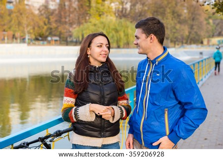 Waist Up of Young Couple Talking Together on Waterfront Pathway with Colorful Railing in Urban Park on Autumn Day - stock photo
