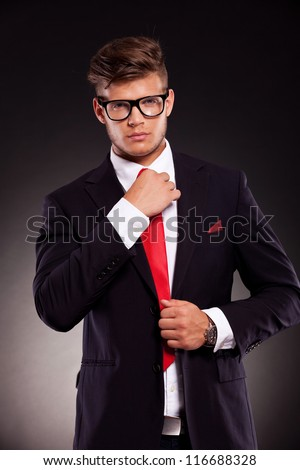 waist-up picture of a young business man fixing his tie and looking into the camera. on dark background - stock photo