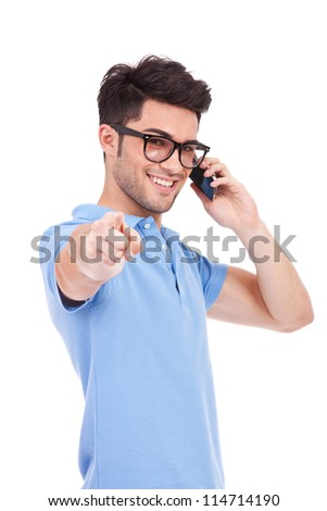 waist-up picture of an attractive young casual man with eyeglasses pointing and looking at the camera while speaking on the phone - stock photo