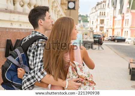 Waist-up portrait of a beautiful couple of tourists standing back to the camera holding a map in their hands and hugging each other while deciding where to go, concept of summer holidays and tourism - stock photo