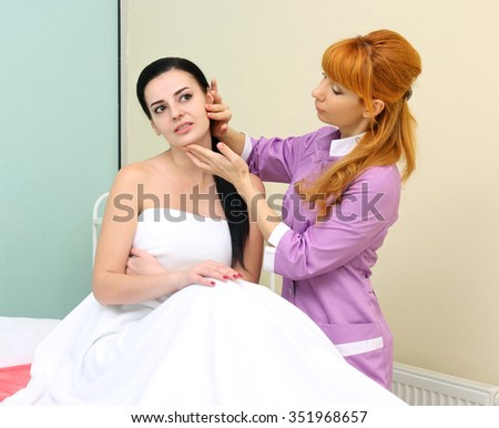 Waist-up portrait of a cosmetologist inspecting skin of her patient a young woman with fresh and clean skin seriously looking at her after a professional cosmetology procedures in a beauty salon