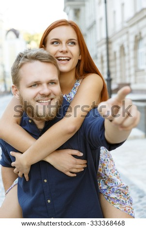 Waist up portrait of a happy couple enjoying their date. Handsome bearded man holding his red-haired girlfriend on his back, both smiling, he is showing her something - stock photo