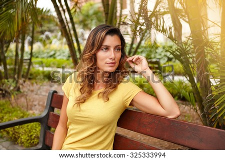 Waist up portrait of a pensive woman in yellow shirt sitting on park bench - stock photo