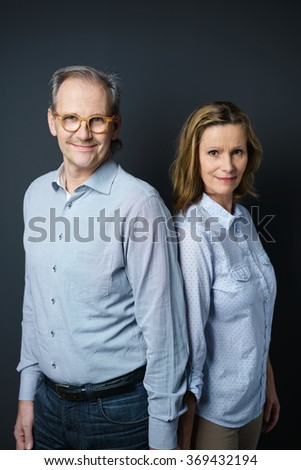 waist up portrait of a self-confident middle-aged couple standing against dark grey background - stock photo