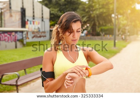 Waist up portrait of a young jogger looking at smart watch while standing outside - stock photo