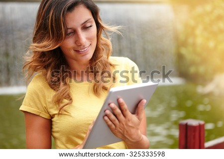 Waist up portrait of a young lady 20-24 years old using tablet when standing by waterfall - stock photo