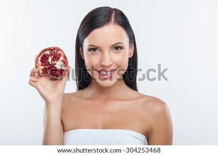 Waist up portrait of attractive girl holding a pomegranate. She is smiling and looking at the camera happily. Isolated on background and copy space in right side - stock photo