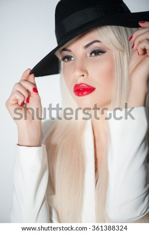 Waist up portrait of attractive young woman evincing her sexuality. She is standing and touching her modern black hat. The lady is looking forward with desire. Isolated - stock photo