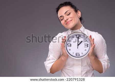 Waist-up portrait of beautiful satisfied girl holding with pleasure and love a big clock in her hands, isolated on grey background with copy place concept of time management - stock photo