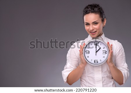 Waist-up portrait of beautiful smiling girl holding with pleasure a big clock in her hands and looking at the camera, isolated on grey background with copy place concept of time management - stock photo