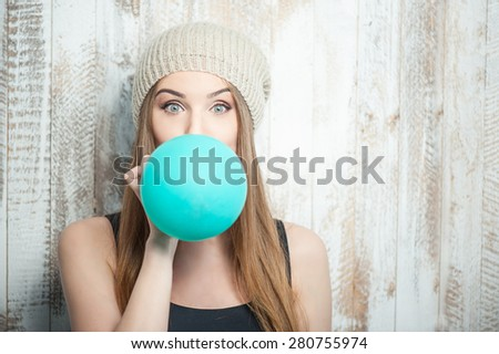 Waist up portrait of cheerful hipster girl with Caucasian appearance, who is standing near the white wall and is blowing up a balloon. - stock photo