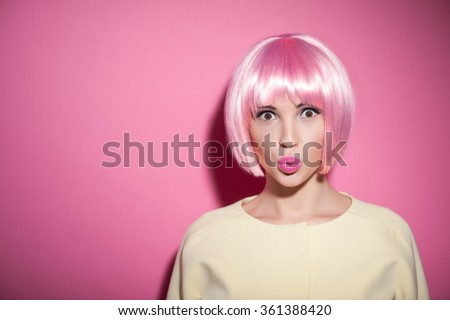 Waist up portrait of cute young woman sending kiss and flirting. She is standing and looking at camera with temptation. The lady is wearing a pink wig. Isolated and copy space in left side - stock photo