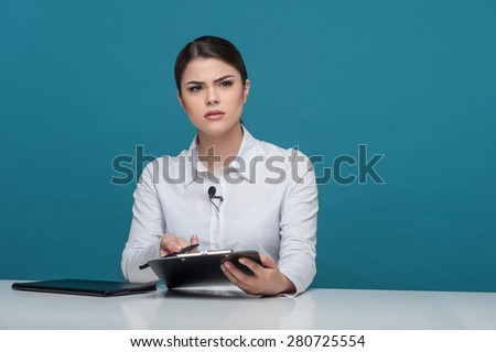 Waist up portrait of elegant woman reporter of Caucasian appearance, who is looking at the camera questioningly and trying to understand something holding the folder and pen in her arms. - stock photo