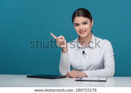 Waist up portrait of elegant woman reporter with brown hair, who is smiling and looking at the camera while sitting at the table and pointing with her finger aside, isolated on a blue background. - stock photo