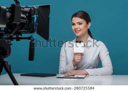 Waist up portrait of elegant woman reporter with brown hair, who is telling the news and smiling looking at the camera while sitting at the desk and holding the microphone. - stock photo