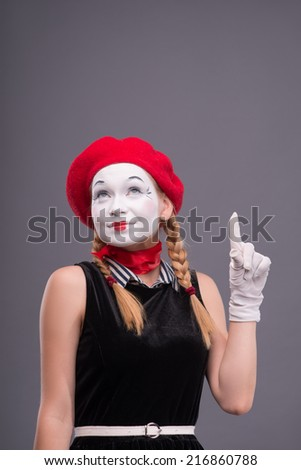 Waist-up portrait of female mime with red hat and white face pretty smiling and looking up and showing sign Attention isolated on grey background with copy place - stock photo