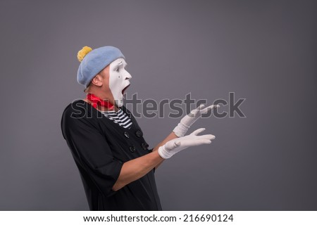 Waist-up portrait of funny and surprised male mime in red head and with white face and opened mouth looking aside and breeding his hands isolated on grey background with copy place - stock photo
