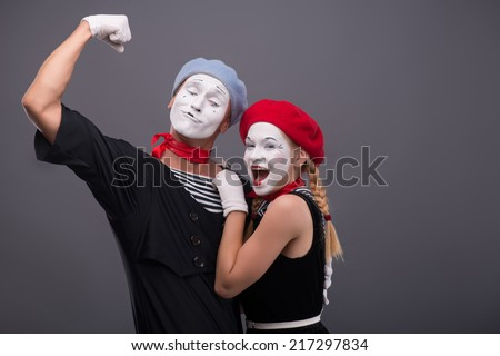 Waist-up portrait of funny  hugging mime couple, male mime looking at his girlfriend and showing his strength, female mime looking at the camera, isolated on grey background with copy place - stock photo