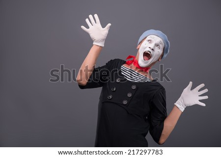 Waist-up portrait of funny male mime with grey hat and white face happy looking up with great surprise and breeding his hands isolated on grey background with copy place