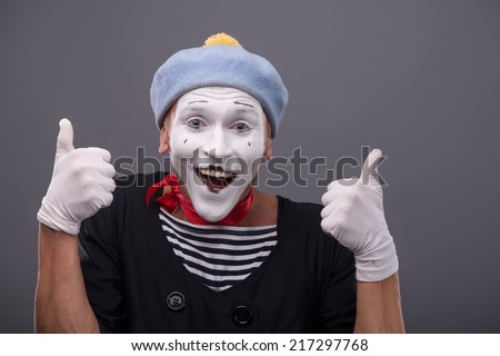 Waist-up portrait of funny male mime with grey hat and white face showing sign OK with both hands and looking at the camera with happy smile isolated on grey background with copy place - stock photo