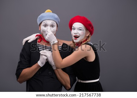 Waist-up portrait of funny mime couple looking at the camera, male mime holding his hands on the chest, female mime touching his nose isolated on grey background with copy place - stock photo