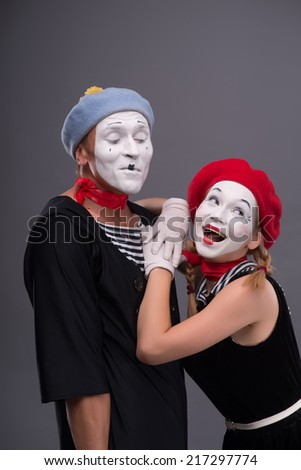 Waist-up portrait of funny mime couple, male mime looking at his girlfriend who is looking aside and leaning on his shoulder, isolated on grey background with copy place - stock photo