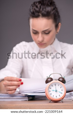 Waist-up portrait of girl sitting at the table in office with a pile of documents and reading them, isolated on grey background with copy place with selective focus on an alarm clock - stock photo
