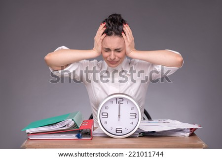 Waist-up portrait of girl sitting at the table with a pile of documents and a clock, holding her head because of headache and crying with closed eyes, isolated on grey background with copy place - stock photo