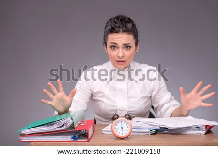 Waist-up portrait of girl sitting at the table with documents and an alarm clock, breeding her hands because she has no time, confused looking at you, isolated on grey background with copy place - stock photo