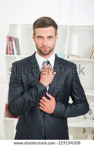 Waist-up portrait of handsome businessman in suit standing in office interior and looking at the camera and tighten his tie with strong and confident face - stock photo