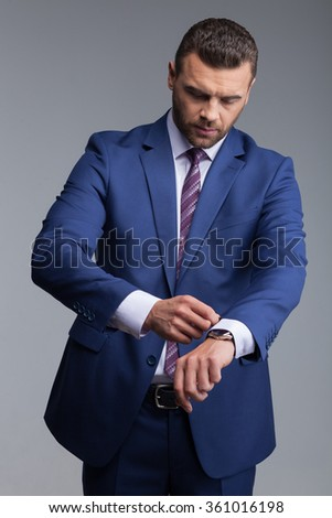 Waist up portrait of handsome businessman is preparing for meeting. He is standing and adjusting a sleeve of his suit with concentration. Isolated - stock photo