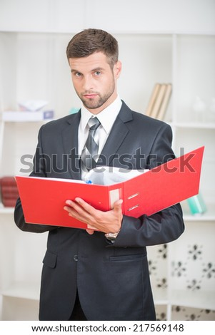 Waist-up portrait of handsome confident businessman standing in office with a red folder in his hands and looking at the camera with serious face - stock photo