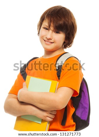 Waist up portrait of happy and smiling teenage boy holding pile of books and wearing backpack on white