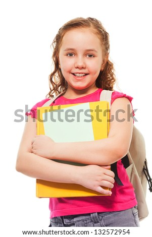 Waist up portrait of happy and smiling teenage girl holding pile of books and wearing backpack on white - stock photo