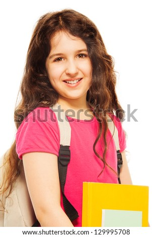 Waist up portrait of happy and smiling teenage girl with pile of books and backpack on white