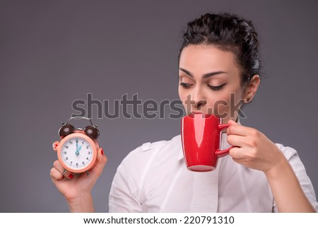 Waist- up portrait of happy girl holding an alarm clock in her hand and drinking from a red cup isolated on grey background with copy place concept of time management and coffee-break - stock photo