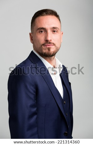 Waist Up Portrait of Man with Facial Hair Wearing Navy Blue Suit Staring at Camera - stock photo