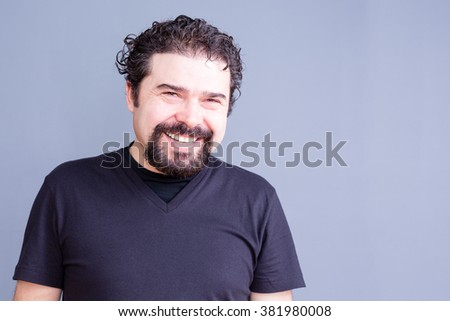 Waist Up Portrait of Mature Man with Beard and Dark Curly Hair Wearing Black T-Shirt and Laughing or Smiling at Camera in Studio with Copy Space