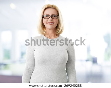 Waist up portrait of middle age businesswoman. Smiling mature woman standing at office and wearing eyewear while looking at camera.  - stock photo