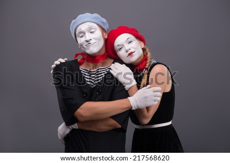 Waist-up portrait of mime couple hugging with love each other, isolated on grey background with copy place, relationships between man and woman  - stock photo