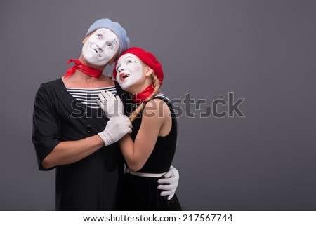 Waist-up portrait of mime couple hugging with love each other isolated on grey background with copy place, looking aside together and pretty smiling  - stock photo