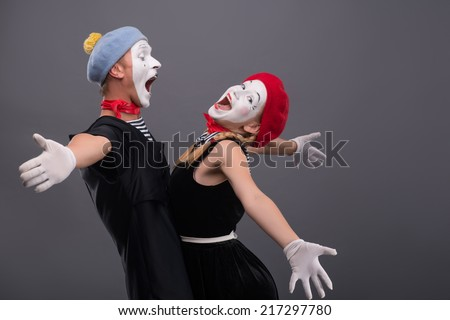 Waist-up portrait of mime couple wanting to hug each other, female mime looking at the camera, male mime laughing and looking at his girlfriend isolated on grey background with copy place - stock photo