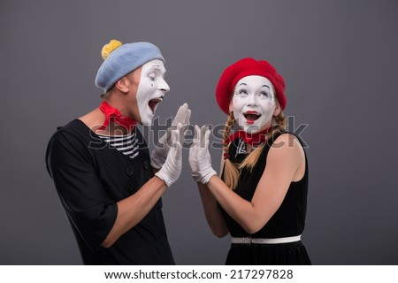 Waist-up portrait of mime couple with white faces clasping each other hands,  female mime looking aside, male mime lovely smiling isolated on grey background with copy place - stock photo