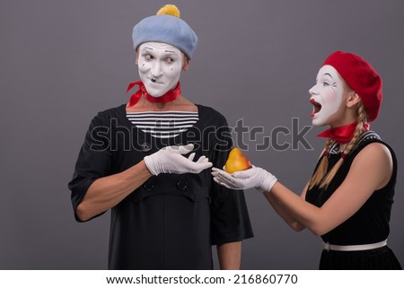 Waist-up portrait of mime couple with white faces, female mime giving a yellow pear to male mime looking on her isolated on grey background with copy place - stock photo