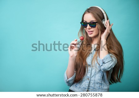 Waist up portrait of pretty hipster girl with Lollipop and glasses, who is looking mysteriously at the camera smiling and singing lovely listening to music, while touching the headphones. - stock photo