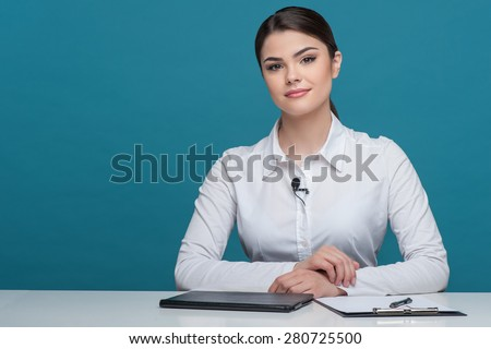 Waist up portrait of pretty woman reporter with brown hair, who is telling news and looking seriously at the camera, sitting at the table on which there is notebook folder and pen, isolated on a blue - stock photo